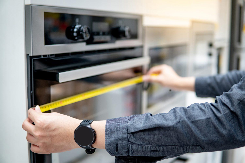 Male interior designer hand using tape measure on oven in the ki